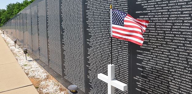 Granite Stone Wall Memorial with white cross and American flag